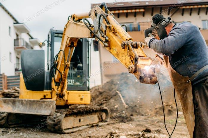 Bau- und Baustelle, gebrochener Bagger und professioneller Schweißer