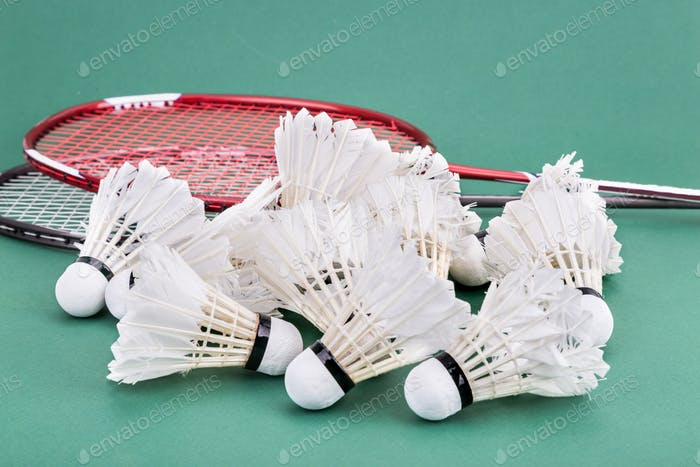 Group of worned out badminton shuttlecock with rackets on court