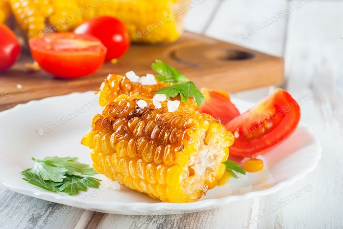 Tasty Barbecue corn cobs with herbs, vegetables and salt on a white plate and a white wooden table