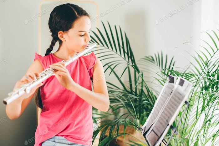 Mädchen spielt die Flöte zu Hause.