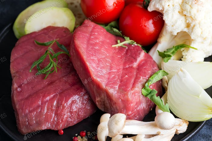Raw beef steak on the bone with fresh vegetables in a pan on a dark stone background