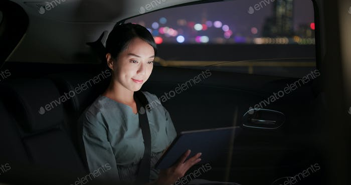 Woman work on tablet computer on car