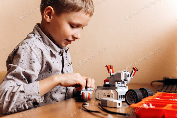Fleißiger Junge in grauem Hemd gekleidet macht einen Roboter aus dem Roboter-Konstruktor am Schreibtisch in der