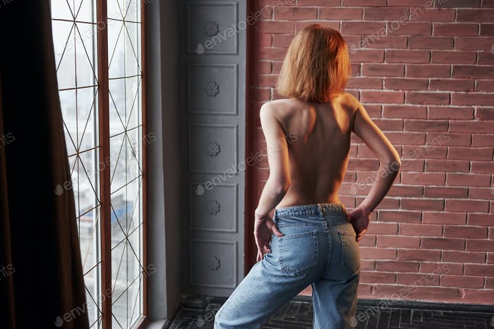 Hot young blonde with bare chest and jeans stands against the window