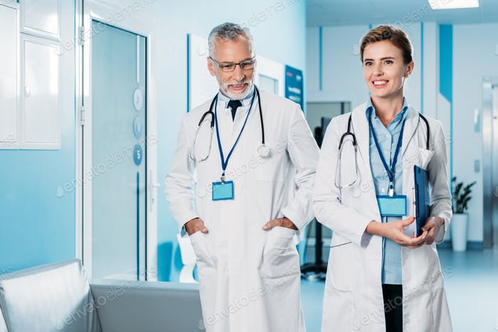 happy female and male doctors with badges and stethoscopes over neck walking in hospital corridor