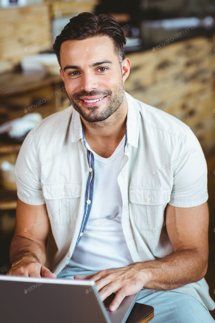 Happy young businessman working at laptop drinking coffee at coffee shop