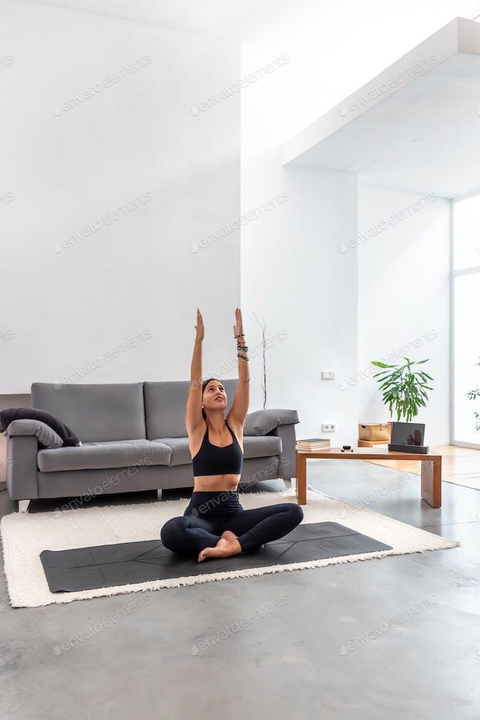 Junge Frau praktiziert Yoga auf ihrem hellen Wohnzimmer zu Hause