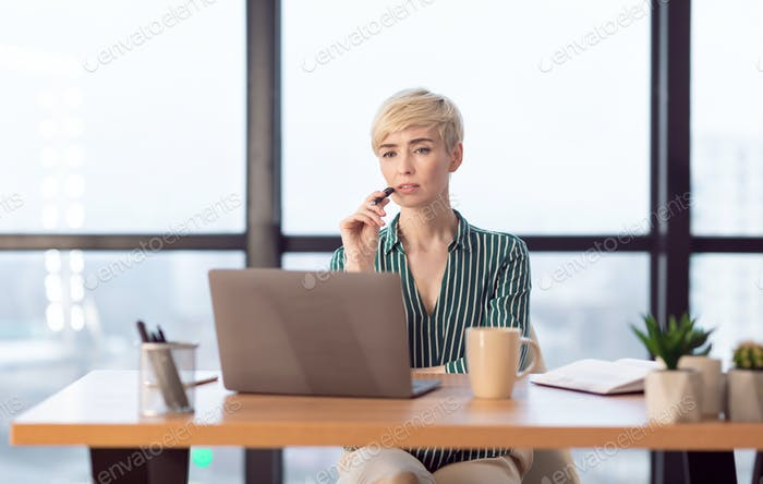 Female Entrepreneur Thinking Sitting At Laptop Working In Modern Office
