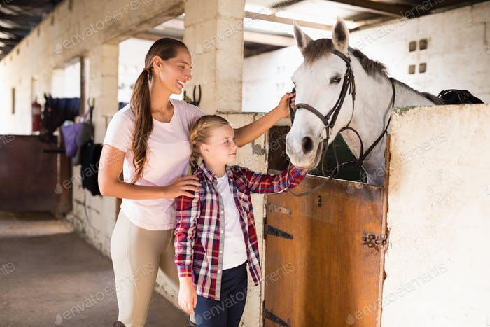 Smiling sisters stroking horse
