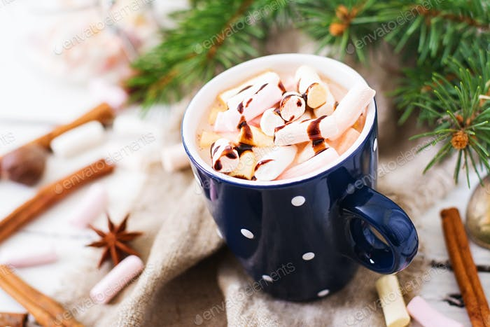 Cup of hot cocoa or chocolate with marshmallow on a light  background