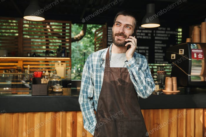 Portrait of cheerful barista guy talking on cellphone in street