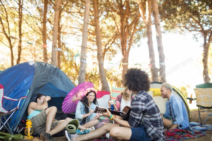 Man playing guitar while sitting with friends at campsite