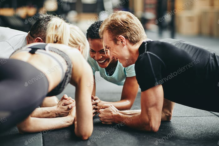 Smiling gym friends planking together during a workout class