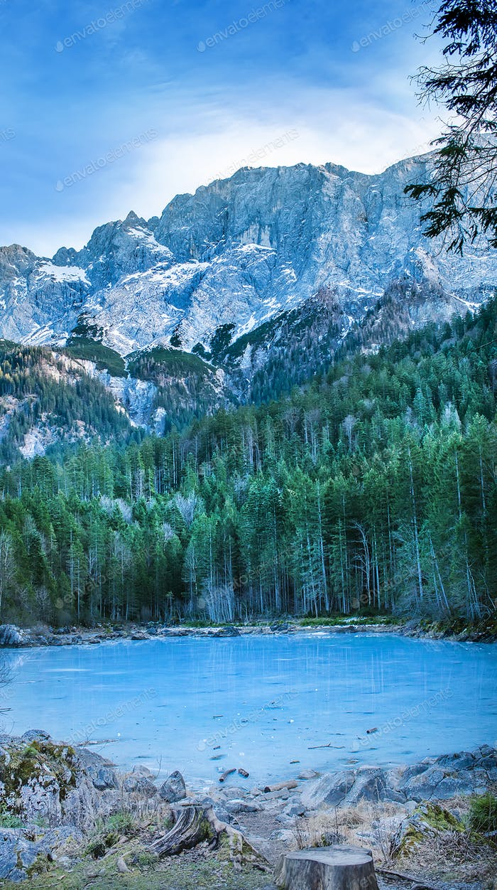 Frozen forest lake in Bavarian Alps near Eibsee lake