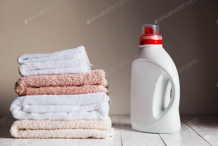 Stack of several coloured and white towels and bottle with cosmetic product