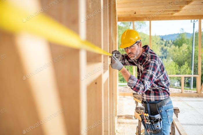 Arbeiter messen Bau auf der Baustelle des Rahmenhauses