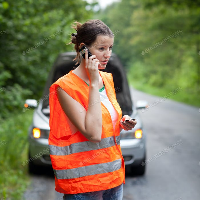 Young female driver wearing a high visibility vest, calling the