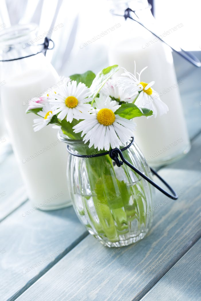 Bottle of Milk and summer flowers on wood background