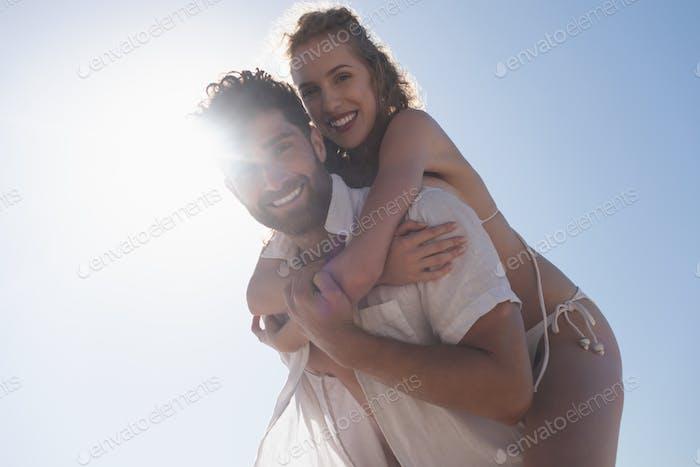 Young Caucasian man carrying pretty Caucasian woman piggyback at beach.