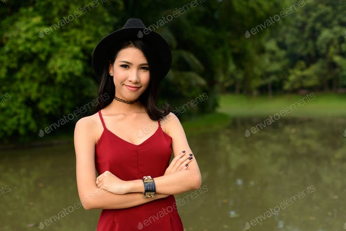 Portrait of young beautiful Asian woman at the park