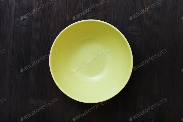 top view of green bowl on dark brown table