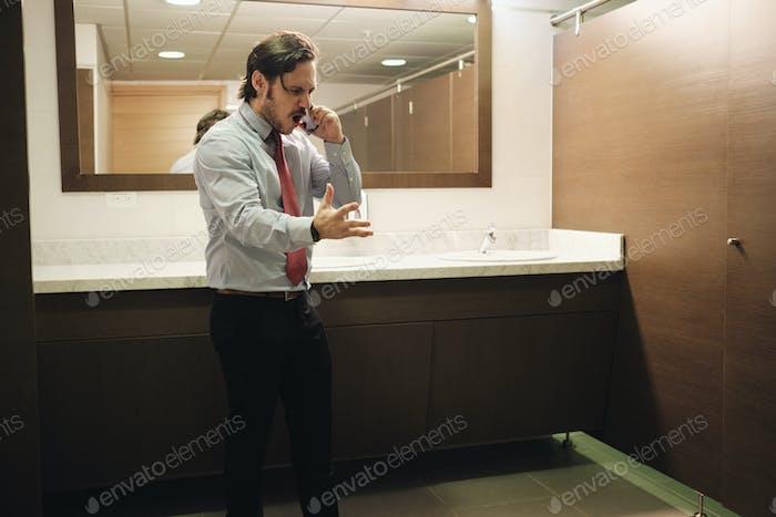 Wütend Business Man Schreien auf Handy in Büro Toilette