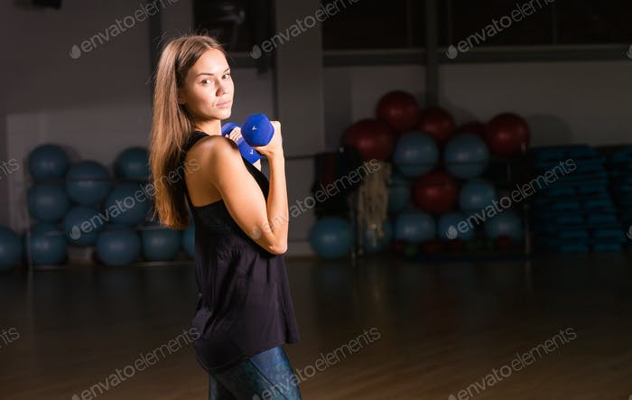 Beautiful young sportswoman doing exercises with dumbbells in gym