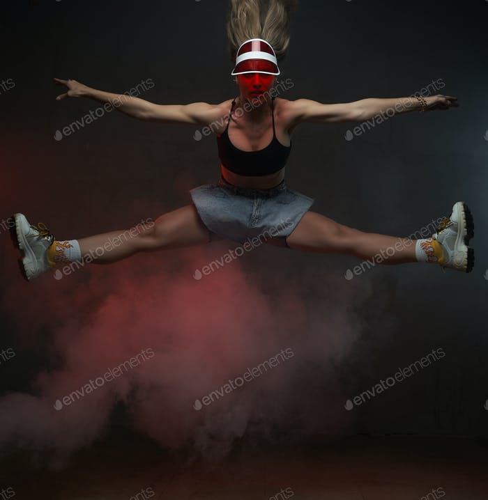 Cheerful dancing girl posing in air in dark smokey background