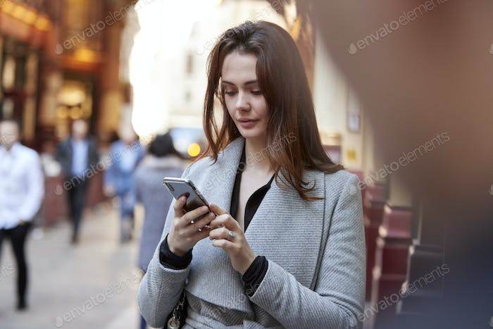 Young white businesswoman standing on a busy London street using smartphone