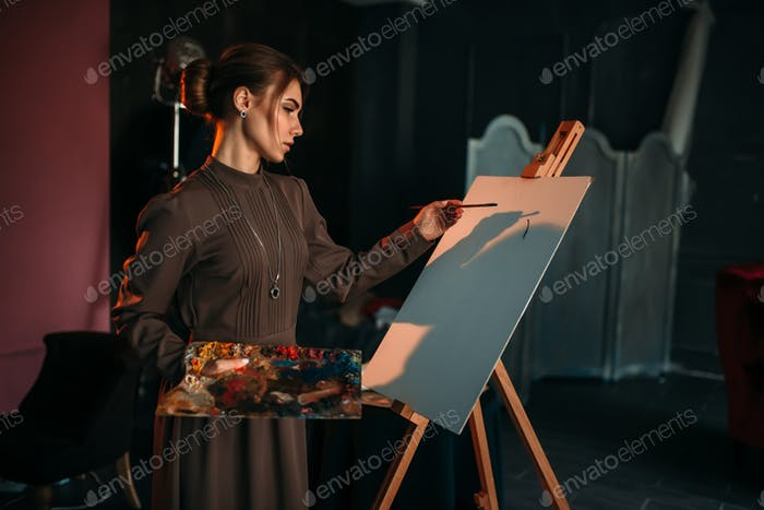 Female painter with brush and palette in hands