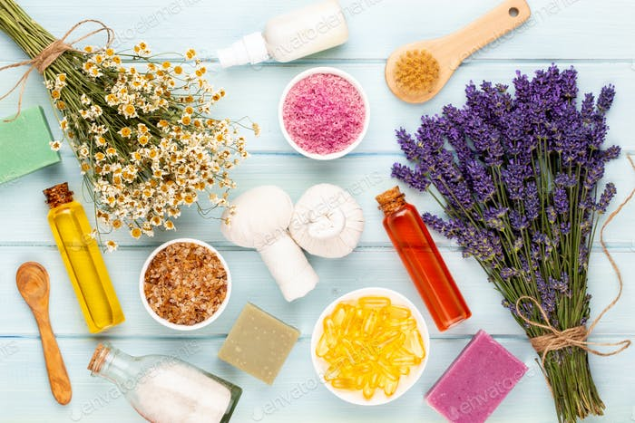 Grooming products and fresh lavender bouquet on white wooden table background.