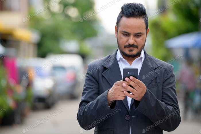 Portrait of bearded Indian businessman using phone outdoors