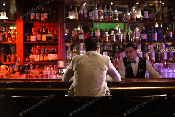 Back view of a man ordering drink to a bartender