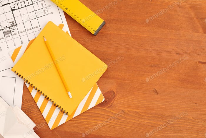 Flatlay of yellow copybooks, ruler and pencil surrounded by unfolded blueprints