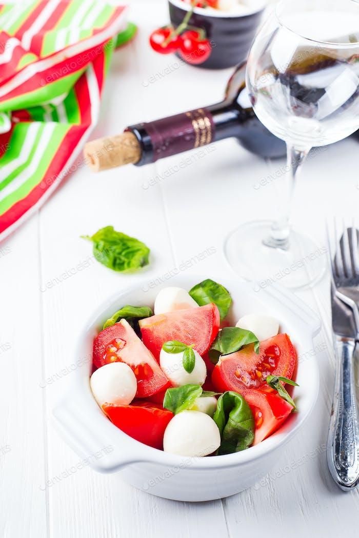Caprese salad with mozzarella, tomato, basil and balsamic vinegar arranged on white bowl