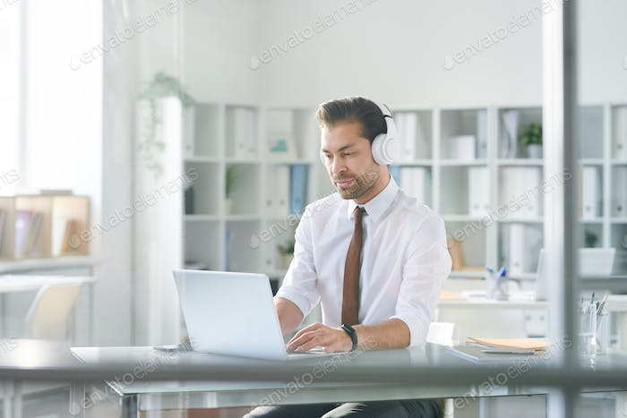 Young concentrated businessman in headphones typing on laptop keypad