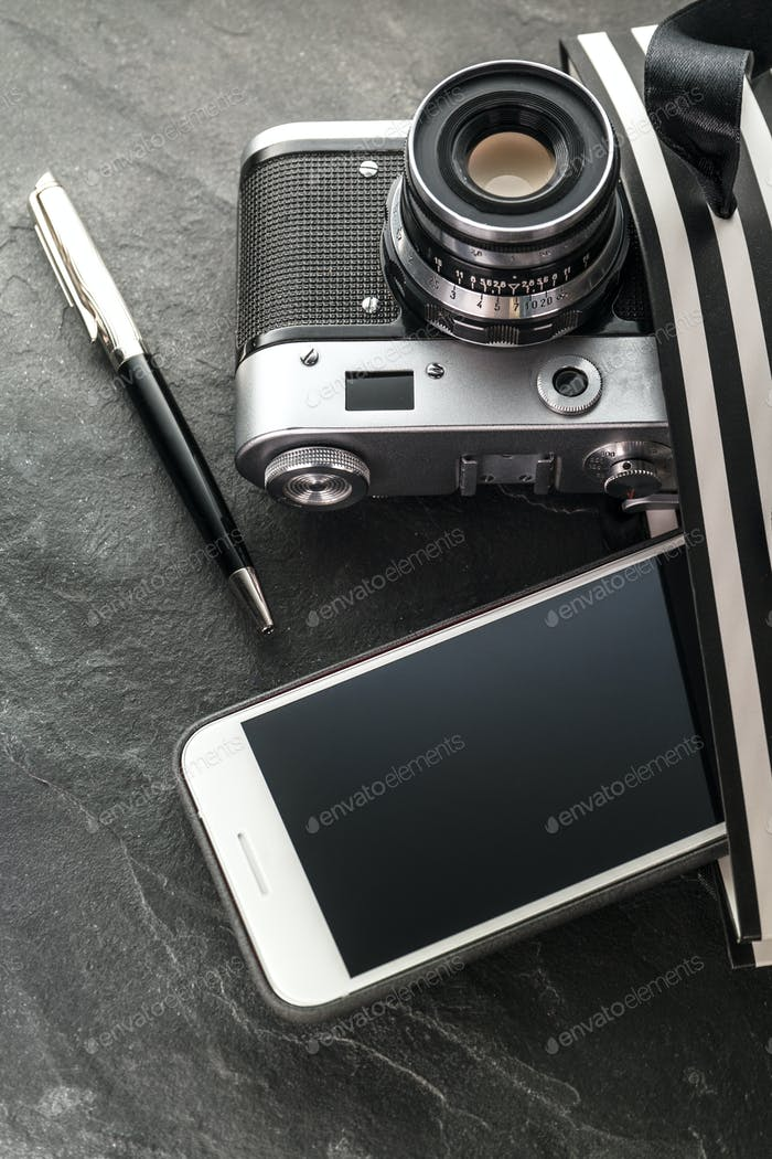 Phone, camera, pen in a black bag with white stripes close-up