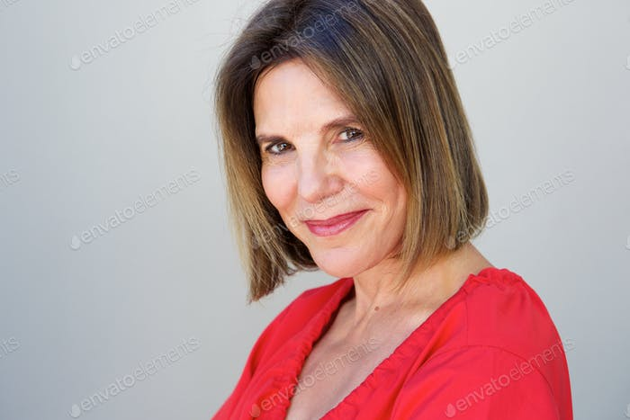 attractive older woman smiling against gray background