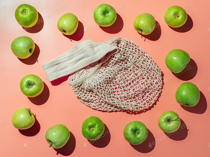 Textile string shopping bag and appes on orange bg