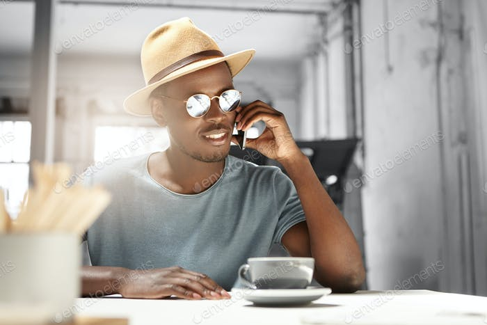 Fashionable and stylish of attractive young black man in headwear and sunglasses talking on mobile p