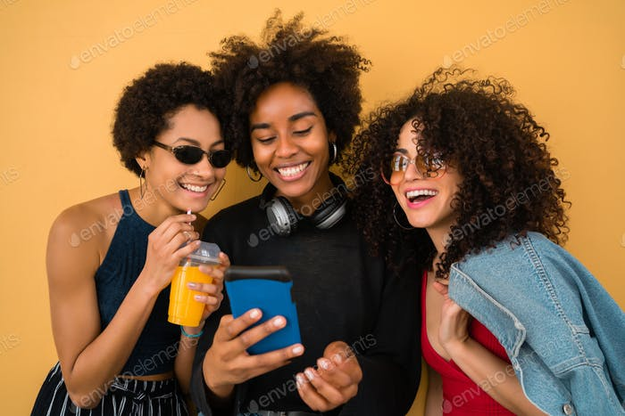 Three Afro friends using mobile phone.