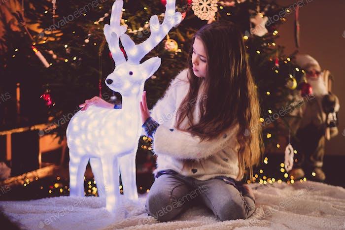 Kleines Mädchen unter Weihnachtsbaum zu Hause