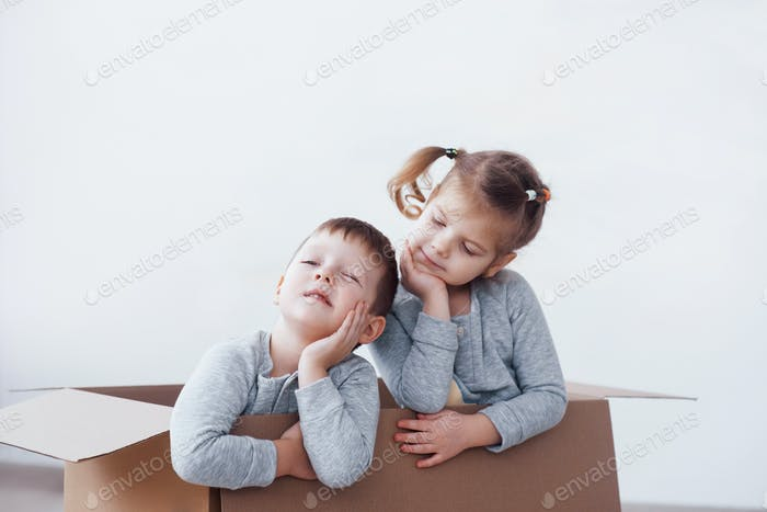 Two a little kids boy and girl playing in cardboard boxes. Concept photo. Children have fun