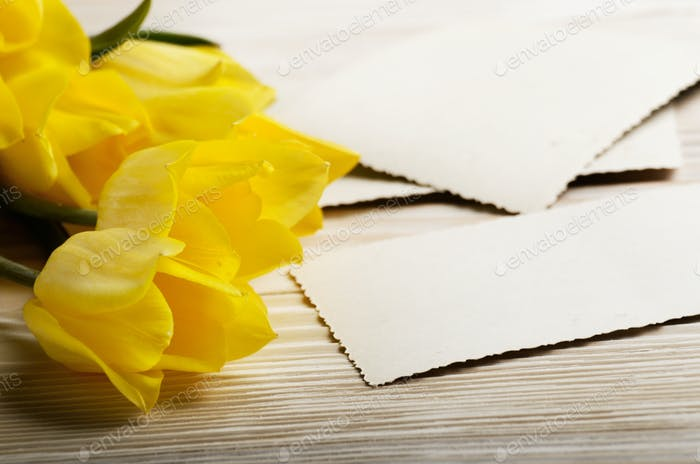 Yellow tulips and blank greeting card on natural wooden backgrou