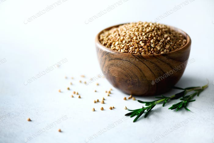 Roasted organic green buckwheat in wooden bowl and rosemary on grey background. Copy space. Food