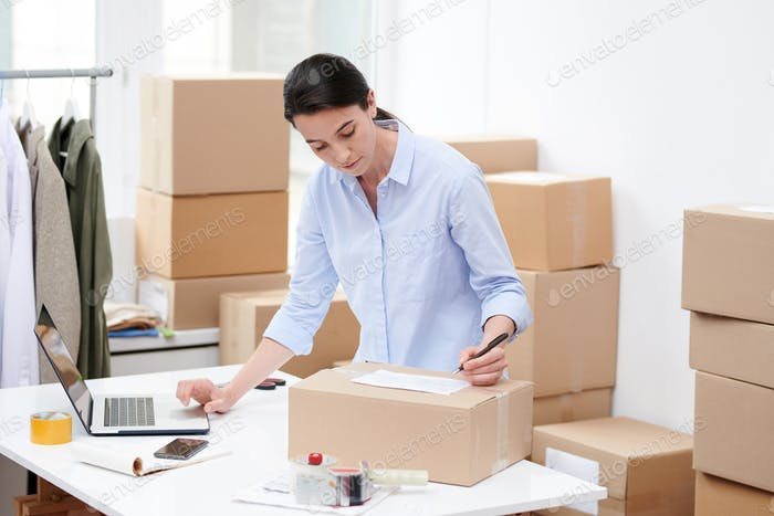 Young female manager of online shop writing down address of client on top of box
