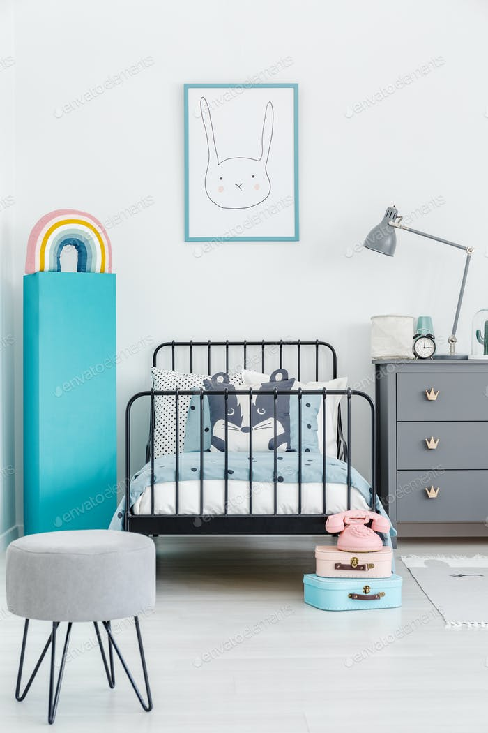 Child's bed with black metal frame in the middle of a pastel, sc