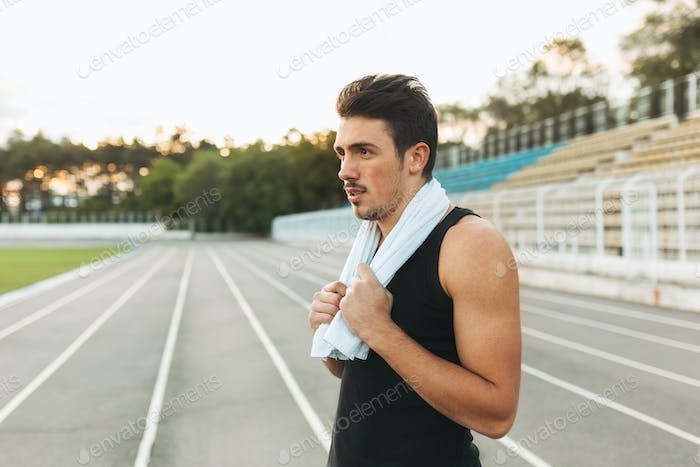 Portrait of a  fitness man with towel on shoulders