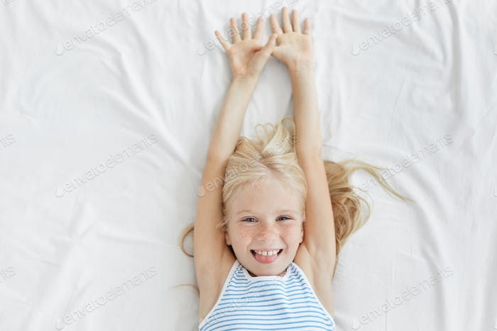 Bedtime concept. Adorable female child with freckles all over her face relaxing in bed after good sl