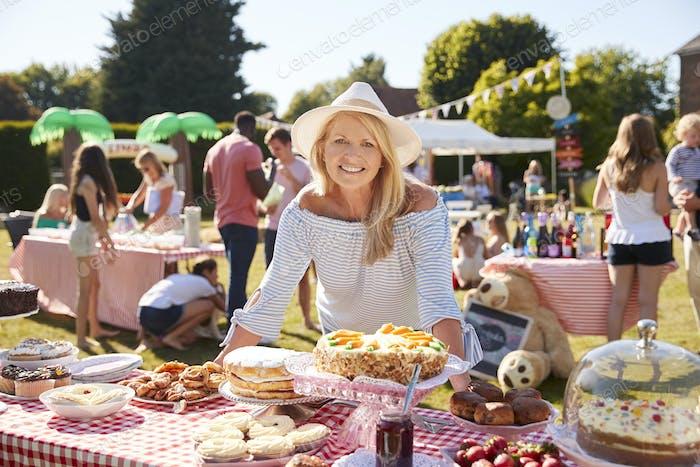 Porträt von Reifen Frau Serving auf Kuchen Stall bei Busy Sommer Garten Fete